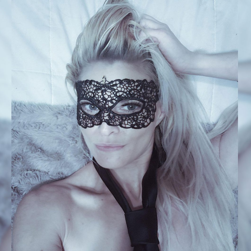 Lilith Veiled wearing a black mask and tie